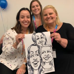 Three women smiling with the caricature they had drawn at a party.